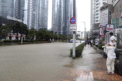 BUSAN (COREA DEL SUR).- Surcoreanos observan el agua que anega una calle de la ciudad de Busan tras el paso del tifón Chaba, en Corea del Sur. Al menos cinco personas han muerto y una permanece desaparecida por el tifón Chaba, que provocó hoy intensos vientos y lluvias a su paso por las regiones meridionales de Corea del Sur, informó el Ministerio de Seguridad de Seúl. Los muertos se produjeron en diversos accidentes provocados por el temporal en las ciudades surorientales de Busan y Ulsan y también en la isla meridional de Jeju, puerta de entrada del Chaba a Corea del Sur. EFE