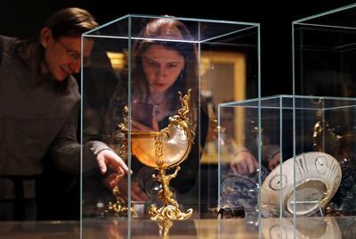 """MOSCÚ (RUSIA).- Visitantes contemplan el """"Nautilus Goblet"""" (i) (lit. El cáliz Nautilus) durante la exposición """"Fascination of Reality. Dutch Burger House Interior of the 17th Century"""" (lit. Fascinación de Realidad. Interior de la casa holandesa Burguer del siglo XVII) en el museo Pushkin en Moscú, Rusia. La exposición incluye cerca de 20 cuadros de grandes maestros holandeses del siglo de oro y otros objetos. La exposición en el museo Pushkin de Bellas Artes y en otros museos de Europa Occidental comenzará del 11 de octubre de 2016 hasta el próximo 1 de enero de 2017. EFE"""