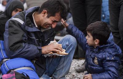 """GEVGELIJA (MACEDONIA).- Instantánea del fotógrafo macedonio de EPA Licovski titulada """"Esperanza 2015"""", en la que un niño consuela a su padre desesperado en la huida desde Pakistán a Europa, por la que recibió hoy la medalla de bronce a la """"Fotografía del Año"""" en los Premios Lead, galardones alemanes para medios escritos y digitales. EFE"""