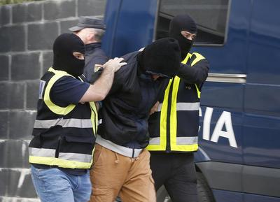 """SAN SEBASTIAN, ESPAÑA.- Agentes de la policía trasladan al presunto yihadista detenido hoy en San Sebastián, acusado de """"captar"""" y """"radicalizar"""" a nuevos terroristas, tras el registro efectuado en su vivienda de la calle Lugaritz, un bloque de viviendas de protección oficial en el que también están situados dos pisos de jóvenes tutelados por la Diputación de Gipuzkoa. Este hombre, un marroquí con permiso de residencia en España, ha sido detenido en el marco de una operación desarrollada por la Policía en San Sebastián y Gijón, ciudad esta última en la que ha sido detenido un segundo presunto yihadista. EFE"""