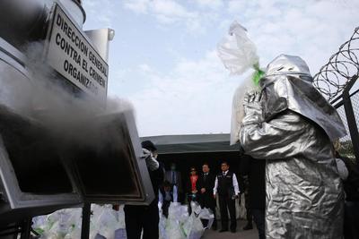 LIMA (PERÚ).- Un miembro de la policía antidrogas de Perú deposita bolsas de estupefacientes al caldero donde son incinerados 7,763.7 kilogramos incautados de narcóticos, los cuales corresponden al cuarto proceso de destrucción de drogas del año, en Lima (Perú). EFE