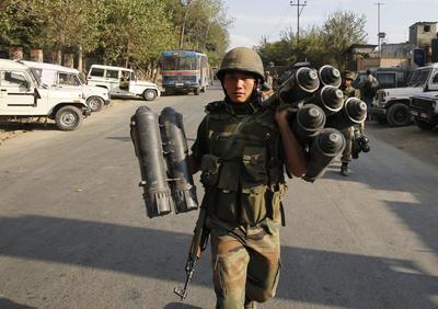 """PAMPORE (INDIA).- Un soldado indio carga con munición a su salida del instituto de formación de Pampore, al sur de Srinagar, capital estival de la Cachemira india. Las tropas indias mataron a dos insurgentes que permanecían atrincherados desde la mañana del lunes en un edificio gubernamental de la Cachemira india y pusieron final a una operación de tres días para reducirlos, informaron hoy fuentes oficiales. El portavoz del Ejército, mayor general Ashok Narula, confirmó en la región norteña que dos personas fueron """"eliminadas"""" y agregó que las fuerzas de seguridad recuperaron además dos armas del lugar, el instituto de formación de Pampore. EFE"""