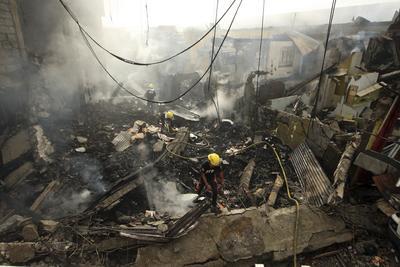 MANILA (FILIPINAS).- Unos bomberos filipinos caminan entre los restos de un incendio que se produjo en una fábrica de fuegos artificiales en Bocaue, Bulacan, Manila, Filipinas. Al menos una persona ha muerto y veinticuatro han resultado heridas a consecuencia del suceso. EFE/Kenjie Hasegawa