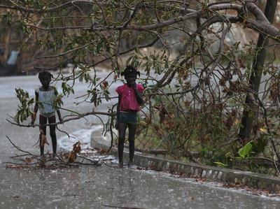 JEREMIE (HAITÍ).- Dos niñas se protegen de la lluvia en el camino que une Jeremie y Les Cayes, dos de las zonas afectadas por el paso del huracán Matthew en Jeremie (Haití). Miembros de la Organización Panamericana de la Salud (OPS) avanzan en la evaluación de la situación sanitaria de las comunidades del sur y suroeste de Haití, las más castigadas por el huracán Matthew, y coordinan desde el terreno la gestión de la ayuda humanitaria que está por llegar. EFE