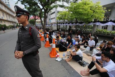 BANGKOK (TAILANDIA).- Un oficial tailandés (i) permanece junto a un grupo de mujeres que sostienen retratos del rey Bhumibol Adulyadej mientras lamentan por su muert, en Bangkok. Con llantos, lágrimas y rezos reaccionaron hoy los miles de tailandeses congregados en el Hospital Siriraj de Bangkok al conocer la noticia de la muerte del monarca, Bhumibol Adulyadej, a los 88 años. El heredero al trono, el príncipe Vajiralongkorn, ha pedido un periodo de duelo antes de subir al trono. EFE