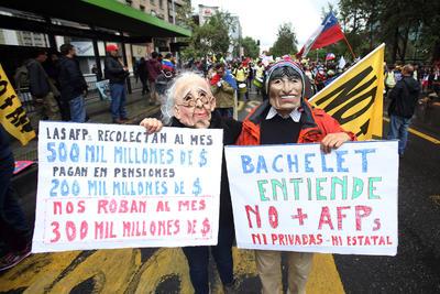 SANTIAGO DE CHILE (CHILE).- Un grupo de personas protestan, en la tercera marcha nacional contra el actual sistema privado de pensiones impuesto en 1981, por la dictadura de Augusto Pinochet, en Santiago de Chile (Chile). Los chilenos protestaron a pesar de las bajas temperaturas y las intensas lluvias que han caído en la mayor parte del país. EFE