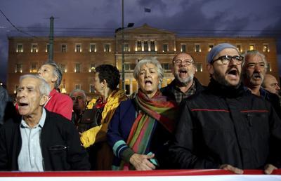 ATENAS (GRECIA).- Manifestantes del sindicato comunista PAME protestan contra la planeada la reforma laboral frente al Parlamento en Atenas, Grecia. EFE