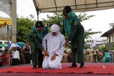 """BANDA ACEH (INDONESIA).- Una mujer es llevada a un escenario por dos policías de la ley islámica o """"sharía"""" por violar la misma, en la Gran Mezquita de Baiturrahman en Banda Aceh, en la región indonesia de Aceh. Varias parejas recibirán hoy entre 10 y 25 latigazos por violar la ley islámica que dice que un hombre y una mujer no pueden tener una cita sin estar casados. La región de Aceh es la única de Indonesia que ha implementado la sharía como fuente del Código Penal. EFE"""