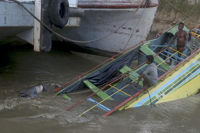 MONYWA (BIRMANIA).- Miembros de los servicios de rescate abordan un barco de pasajeros hundido en el río Chindwin, cerca de la ciudad de Monywa (Birmania). Las autoridades de Birmania (Myanmar) elevaron al menos a 29 el número de muertos en el hundimiento de un barco de pasajeros en un río del oeste del país, con decenas de pasajeros aún desaparecidos, informó hoy la prensa local. EFE