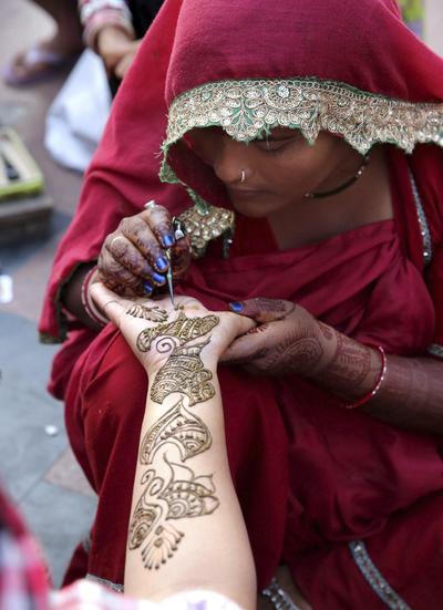 JA05 BHOPAL (INDIA) 18/10/2016.- Una mujer pinta con henna las manos de una mujer en la víspera del Festival Chauth en Bhopal (India) hoy, 18 de octubre de 2016. Durante esta festividad, las mujeres casadas ayunan y rezan por la longevidad y bienestar de sus maridos. EFE/Sanjeev Gupta