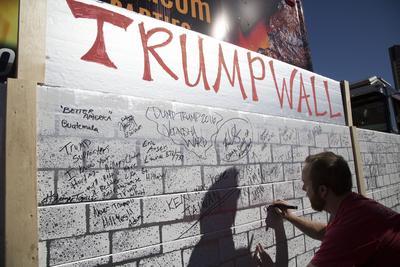 """LAS VEGAS (NV, EE.UU.).- Un manifestante escribe sobre un muro simbólico llamado """"Muro de Trump"""", en la puerta del Hotel Trump en Las Vegas, Nevada, para protestar contra el candidato republicano a la Casa Blanca, Donald Trump. Esta manifestación tuvo lugar coincidiendo con la celebración en esta ciudad del último debate presidencial de las elecciones estadounidenses, que enfrentará esta tarde a Trump y a la aspirante demócrata, Hillary Clinton. EFE"""