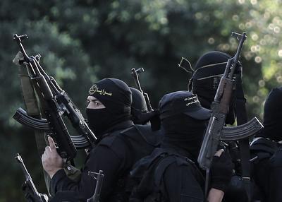 FRANJA DE GAZA.- Militantes de la Yihad islámica sostienen sus armas, durante un desfile militar en la Franja de Gaza. EFE