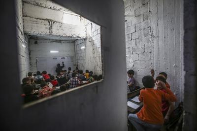 AL-QABOON (SIRIA).- Niños sirios asisten a clase en la escuela al-Hayat school en la región rebelde de al-Qaboon, a las afueras de Damasco, Siria. La escuela de Al-Hayat sufrió un bombardeo del ejército sirio el 5 de noviembre de 2016, causando la muerte de 13 de sus estudiantes. Al día siguiente del ataque, se alcanzó un acuerdo de cese de hostilidades. La escuela ha sido trasladada a un sótano. EFE