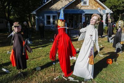 DECATUR (ESTADOS UNIDOS).- Vitsa de dos muñecos por Halloween que representan a los candidatos presidenciales Hillary Clinton (d) como un ángel y Donald Trump (i) como un demonio, junto al ex vicepresidente Dick Cheney (i) en el jardín de una vivienda de Decatour, Georgia, Estados Unidos. EFE