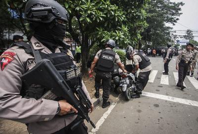 TANGERANG (INDONESIA).- Policías buscan explosivos mientras otros compañeros vigilan en una comisaría de la policía de tráfico en Tangerang (Indonesia). Según medios locales, un hombre de 21 años recibió un tiro en la pierna tras colocar una pegatina de Estado Islámico en un puesto de la policía y atacar con un cuchillo a los policías que estaban de servicio. Tres oficiales resultaron heridos en el ataque. Cuando el atacante fue sometido, la policía encontró pequeños explosivos colocados en los alrededores del lugar del ataque. EFE