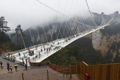 """ZHANGJIAJIE (CHINA).- Centenares de turistas visitan el puente de Zhangjiajie en el parque natural del mismo nombre en la provincia de Hunan, China. Se trata del puente de cristal más alto y largo del mundo, de 430 metros de longitud y 300 de altura. Diiseñado por el arquitecto israelí Haim Dotan e inaugurado hace dos meses, el puente tiene seis metros de ancho, une dos acantilados de la montaña Tianmen (""""Puerta del Cielo"""") a través de 99 paneles con tres capas de cristal y está preparado para que sobre él circulen hasta 800 personas a la vez. EFE"""