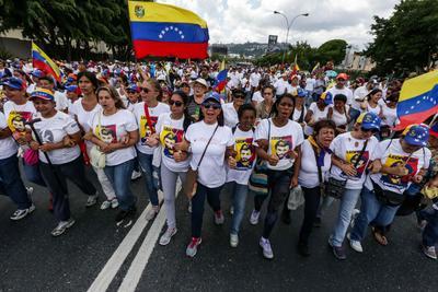 CARACAS (VENEZUELA).- Manifestantes participan en una marcha, en Caracas (Venezuela). Cientos de mujeres marcharon hoy en Caracas para exigir que se realice este año un referendo revocatorio al presidente Nicolás Maduro, un mecanismo que venía impulsando la oposición venezolana desde hace meses y que fue pospuesto esta semana por el Poder Electoral. EFE