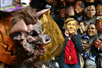 MIAMI (FL, EE.UU.).- Helen Laisel, de la Casa de los Trucos, se prueba una máscara de hule con la imagen de la candidata presidencial demócrata, Hillary Clinton, en Miami, Florida (EE.UU.). Su característico aspecto físico y marcada gestualidad hacen de Donald Trump un blanco fácil para parodias y son una garantía de éxito para los vendedores de disfraces, que en esta temporada de Halloween esperan agotar sus existencias de rubios tupés y expresivas máscaras. En lo que se refiere a servir de modelo para disfraces de Halloween, Trump le gana a su rival demócrata, Hillary Clinton, a la inversa de lo que indican las encuestas sobre la intención de voto para las elecciones del 8 de noviembre. EFE