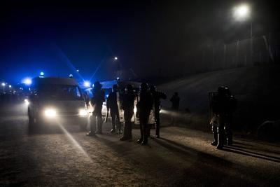 Calais (Francia).- La policía antidisturbios francesa se dispone a intervenir después de los migrantes incendiaran los contenedores de basura junto al campo improvisado 'la jungla' de Calais, Francia. El campamento que cuenta actualmente con más de 7.000 migrantes será desmantelado el 24 de octubre, un proceso que tomará una semana según las autoridades francesas. EFE
