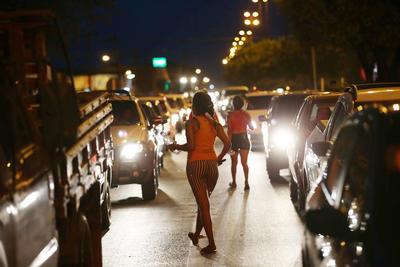 """WASHINGTON, DC (EEUU).- Fotografía de jóvenes venezolanas caminando entre los autos en la ciudad de Boa Vista, en el norte de Brasil, donde venden baratijas, limpian los parabrisas de los automóviles para ganarse unas pocas monedas debido a la crisis en su país. La organización Human Rights Watch (HRW) urgió a que haya una """"fuerte presión internacional"""", y en particular de la región, para que el Gobierno del presidente Nicolás Maduro tome """"medidas inmediatas"""" para abordar la """"profunda crisis humanitaria"""" en Venezuela, en un extenso informe divulgado hoy. """"El Gobierno venezolano ha parecido más rotundo en negar la existencia de una crisis humanitaria que en trabajar para resolverla"""", enfatizó José Miguel Vivanco, director para las Américas de HRW. EFE"""