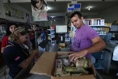 PACARAIMA (BRASIL).- Fotografía de un hombre que muestra un fajo de bolívares en la ciudad de Pacaraima, una empobrecida y pequeña ciudad del norte de Brasil, que se ha convertido en uno de las últimos horizontes en que los venezolanos consiguen la comida y los productos básicos que escasean en su país. Según distintas fuentes consultadas por Efe en esta ciudad de la frontera entre Brasil y Venezuela, entre 1.000 y 1.500 venezolanos cruzan cada fin de semana la línea divisoria, compran alimentos y regresan a su país. EFE