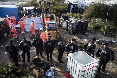 """CALAIS (FRANCIA).- Un grupo policías galos observa el proceso de desmantelamiento de algunas de las tiendas que han configurado el campamento de inmigrantes de Calais, conocido como """"la Jungla"""", en Calais, Francia. La operación para evacuar el centro de inmigrantes de Calais, en la que a mediados de su segunda jornada se ha trasladado ya a más de 3.500 personas, comenzó hoy con el desmantelamiento de parte de sus chabolas. Por el momento, los trabajos se han limitado a desmontar algunas de esas viviendas precarias, a la espera de que en los próximos días lleguen las excavadoras. EFE"""