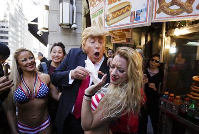 NUEVA YORK (EE.UU.).- Un hombre caracterizado como el candidato a la presidencia de EE.UU. el republicano Donald Trump (c) pretende dar de comer una salchicha a una mujer en bikini durante una manifestación contra a las declaraciones de Trump sobre las mujeres, cerca a la torre Trump en Nueva York (EE.UU.). EFE
