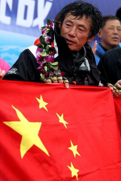 QIGDAO (CHINA).- Fotografía de archivo del 5 de abril de 2013 donde se ve al marino chino Guo Chuan posando con la bandera de China en una ceremonia de bienvenida en la ciudad de Qingdao, al oeste de China. Según informaciones periodísticas de hoy, el equipo de apoyo de Guo Chuan en su intento de navegara de San Francisco hasta Shangai perdió contacto con el desde el 25 de octubre. Chuan partió de San Francisco el 18 de octubre, en su travesía de 20 días. EFE
