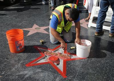 HOLLYWOOD (CA, EE.UU.).- Un trabajador latino repara la estrella del actual candidato republicano a la Presidencia de EE.UU., Donald Trump, en el Paseo de la Fama de Hollywood, California. La estrella fue destrozada por un vándalo durante la pasada madrugada. EFE