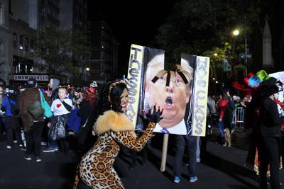 """Meghan Mitchells, quien decidió disfrazarse como una mujer atacada por Trump, cuya máscara se posaba tras ella como si la acosara, expresó que el comportamiento del candidato pertenece a un """"desfile del horror""""."""