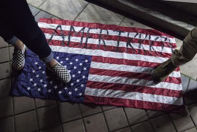 """Manifestantes pisaron una bandera estadounidense con la palabra """"Amerikka"""" escrita en ella ante el Ayuntamiento de Oakland."""