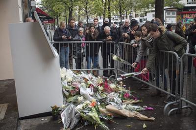 Una mujer deja flores en  honor a las víctimas del ataque.