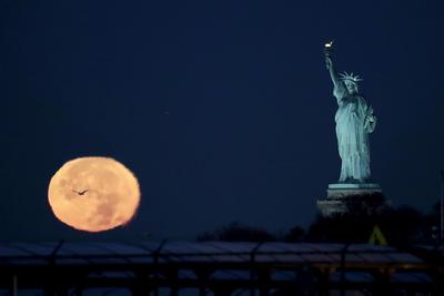 """Nueva York, con su Estatua de la Libertad, fue uno de los múltiples escenarios en donde pudo apreciarse la """"superluna"""", un fenómeno que ayer registró su mayor intensidad desde 1948."""