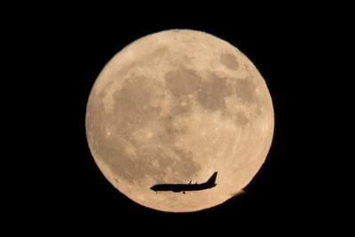 China. Un avión tiene como fondo la superluna, visto desde Beijing, China.