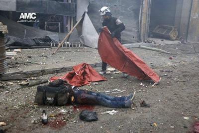 Soldado del miembro de la Defensa Civil, conocidos como cascos blancos, cubriendo el cuerpo de un fallecido tras el impacto de una bomba en el barrio de Yeb al Quebeh en Alepo.