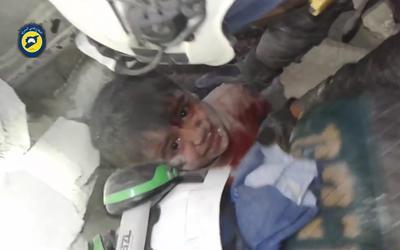 Rescatistas tratando de sacar a un niño atrapado bajo los escombros de un edificio en el barrio de Maadi, Alepo, Siria.