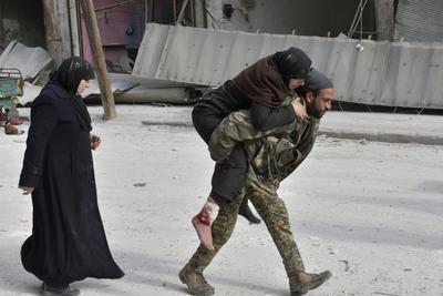 Soldado sirio que traslada a hombros a una mujer herida después de que el gobierno tomara el control de la zona en Alepo.
