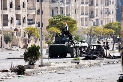 Soldados sirios patrullan en su vehículo blindado junto a edificios dañados en las aldeas occidentales de Alepo del distrito de al-Assad.