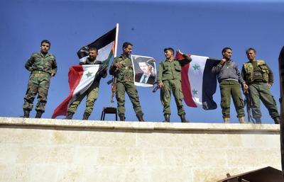Miembros del Ejército Árabe Sirio (SAA) ondeando banderas nacionales y sujetando carteles con el rostro del presidente, Bachar al Asad, en ya tomada localidad de al-Hader, en Alepo.