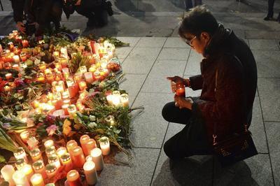 Un hombre enciende una vela en honor a las víctimas del atentado.