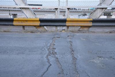 Baches. En el suelo se observan grietas y un desnivel irregular al paso de los vehículos, además de baches que han crecido con el paso del tiempo.
