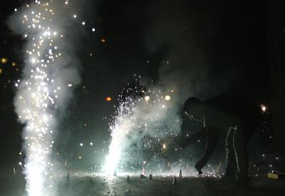 Un hombre en Mumbai, India, enciende fuegos artificiales en celebración de año nuevo.