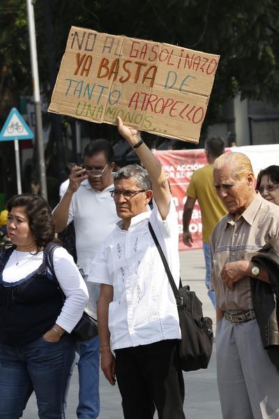 El pueblo se cansa de tanta pinche tranza', gritaban las personas que se reunieron para marchar rumbo al Zócalo capitalino. Al arribar, gritaron frente a la puerta del Palacio Nacional. Los asistentes portaban banderas con leyendas como 'No más gasolinazos' y 'Fuera Peña Nieto'.