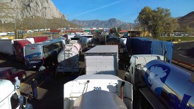 Vehículos pesados, como tráileres y camiones de tres toneladas, parados en la autopista dejando pasar únicamente vehículos pequeños y de pasajeros, sin pagar la cuota.