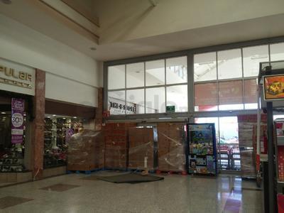 Trabajadores de un centro comercial colocaron diversos productos a manera de barrera para impedir el acceso en un eventual intento de saqueo.