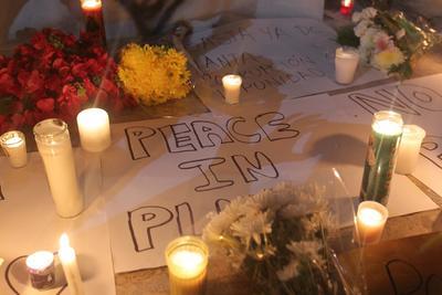 A fuera de la discoteca se encontraban carteles con mensajes de paz acompañados de velas y flores.