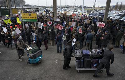 Un grupo de personas se concentró a las 14:00 horas frente a una de las terminales del JFK para protestar contra las medidas aprobadas este viernes por el presidente estadounidense, Donald Trump.