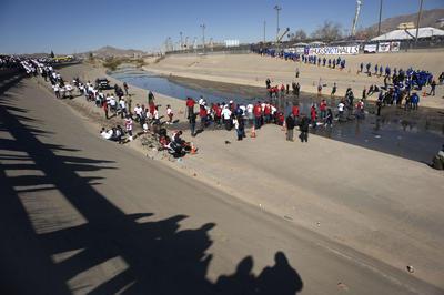 Para que las familias pudieran cruzar la línea divisoria sin tener que caminar por el agua del río, algunos de los organizadores construyeron un puente con tablas y neumáticos.