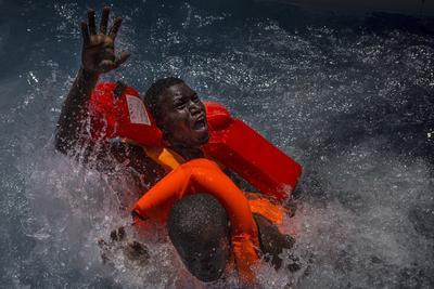 """Imagen tomada por el fotógrafo británico Mathieu Willcocks que ha sido galardonada con el tercer premio en historias de """"Noticias de Actualidad"""", en la que aparecen dos hombres que luchan por mantenerse a flote durante su rescate en alta mar entre las costas de Libia e Italia."""