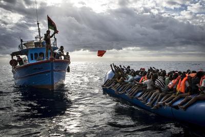 """Imagen tomada por el fotógrafo británico Mathieu Willcocks que ha sido galardonada con el tercer premio en historias de """"Noticias de Actualidad"""", en la que aparecen pescadores libios que lanzan chalecos salvavidas a inmigrantes que viajan a bordo de una patera en alta mar entre las costas de Libia e Italia."""